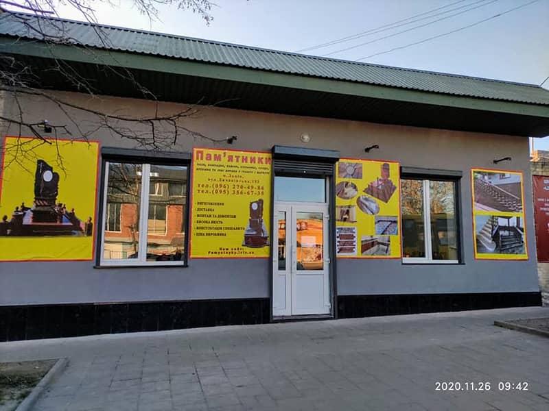 Фасад та територія магазину Граніт у Львові. Банери з гранітними виробами на фасаді