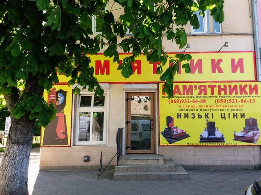 Фасад магазину з рекламними вивісками та головним входом