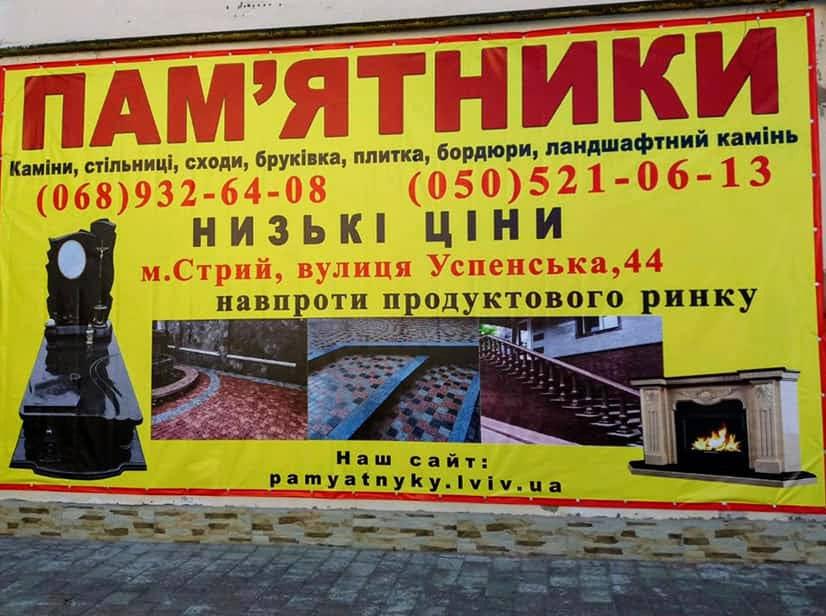 Велика вивіска на стіні магазину з зображеними контактними даними і прикладами гранітних товарів